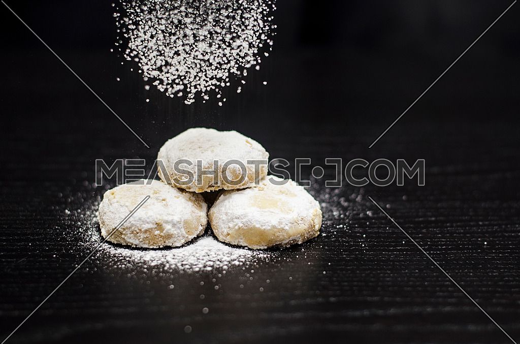 3 kahks on a black table and white sugar in getting sprinkled on them while the flying sugar appears in the frame