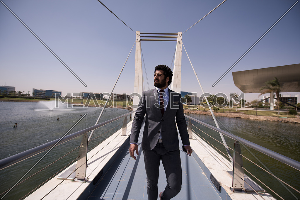young middle eastern businessman walking across modern bridge