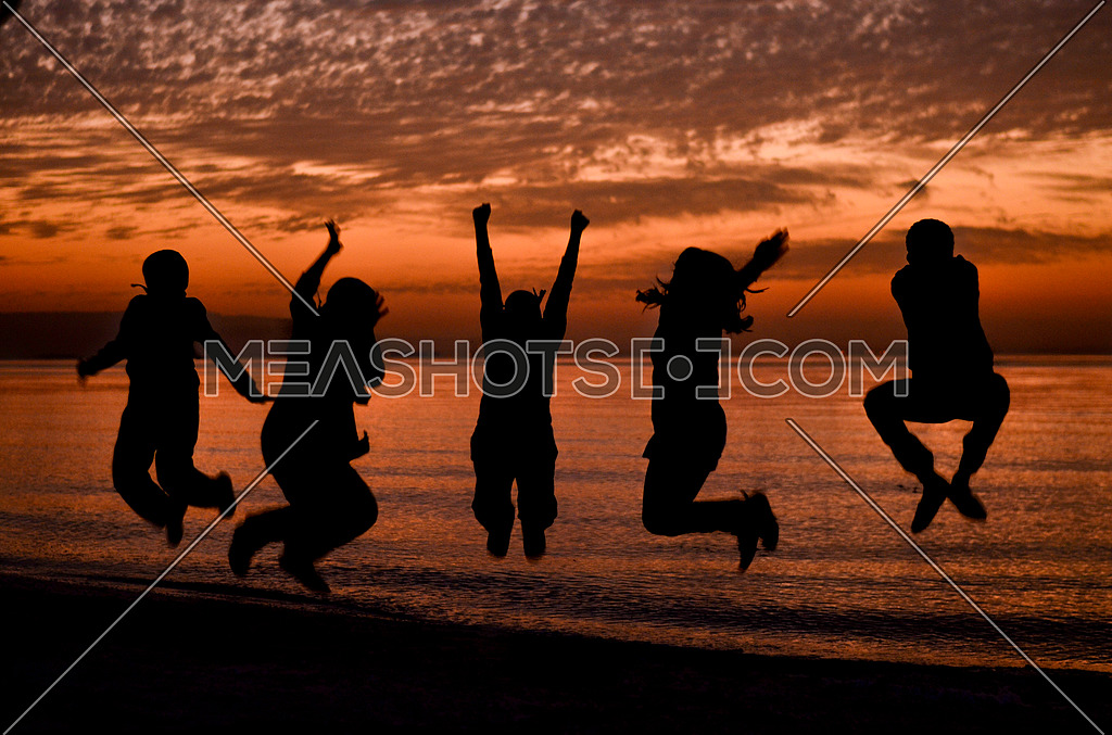 five friends jumping on the beach during sunset magical hour