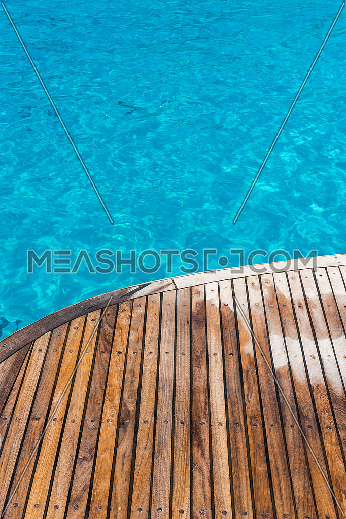 In the pictured curved wooden deck wet and in the background ocean blue / turquoise.