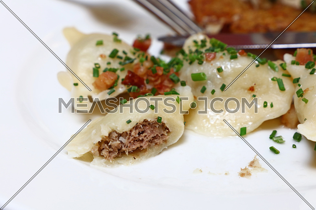 Plate of pierogi, meat stuffed filled dumplings with bacon crisps and green chive, traditional East Europe cuisine meal popular in Poland, Ukraine, Slovakia, Russia, close up, high angle view
