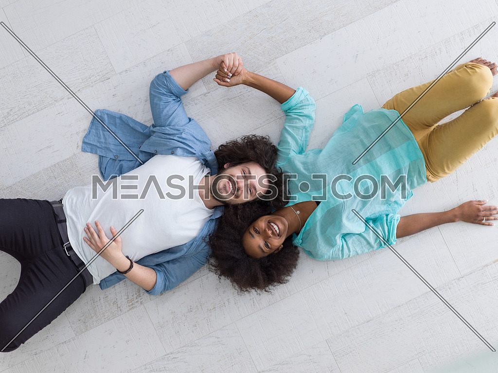 top view 0f Cheerful young multiethnic couple lying on floor and smiling
