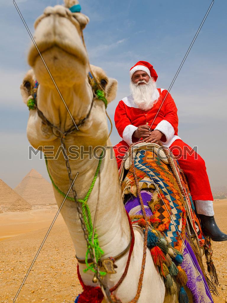 santa claus riding a camel in pyramids desert in Egypt Christmas concept