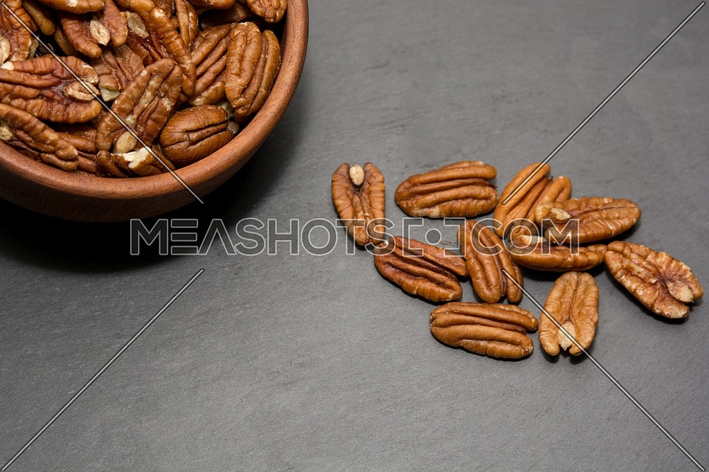 Tasty pecan in wooden bowl on stone old background.