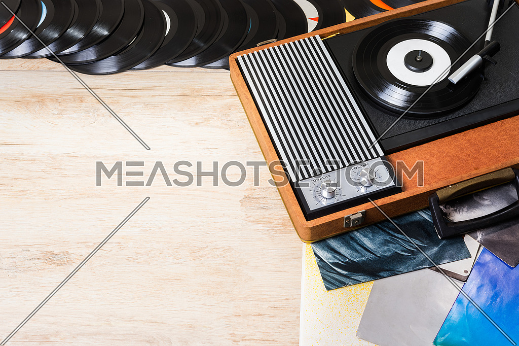 Gramophone with a vinyl records on wooden table, top view and copy space.