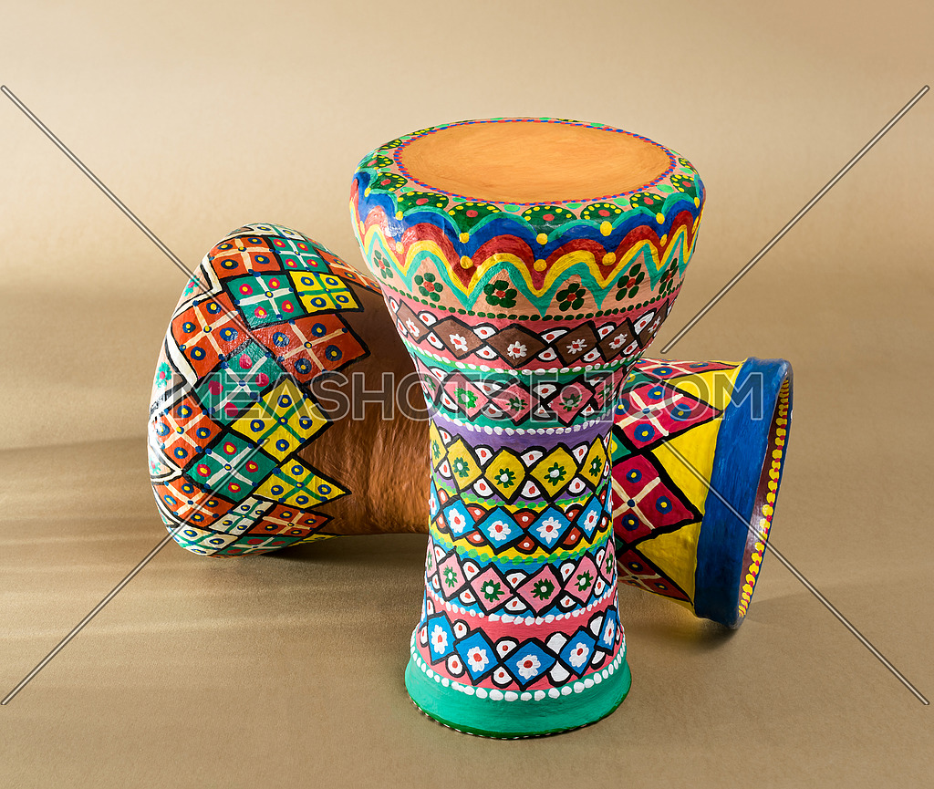 Two decorated colorful pottery goblet drums (chalice drum, tarabuka, darbuka) on background of wooden table with vanishing shadow lines