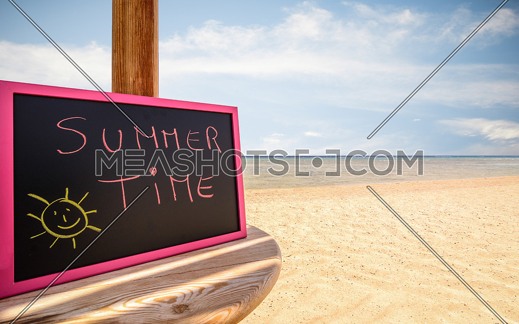 In the picture a beach umbrella which is small blackboard with the words ( Summer Time ) in a beach in the afternoon .