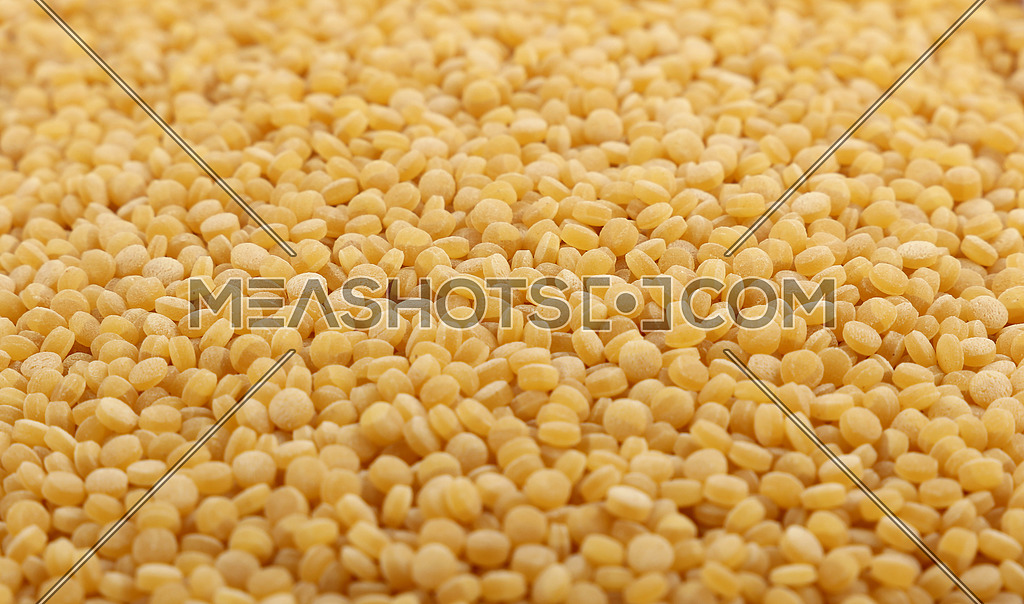 Traditional ptitim pasta (Palestinei or pearl couscous) close up pattern background, low angle view, selective focus