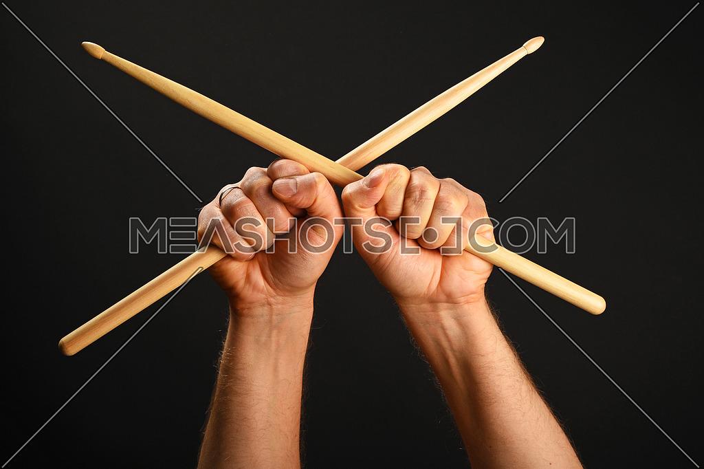 Two man hands holding crossed wooden drumsticks over black background