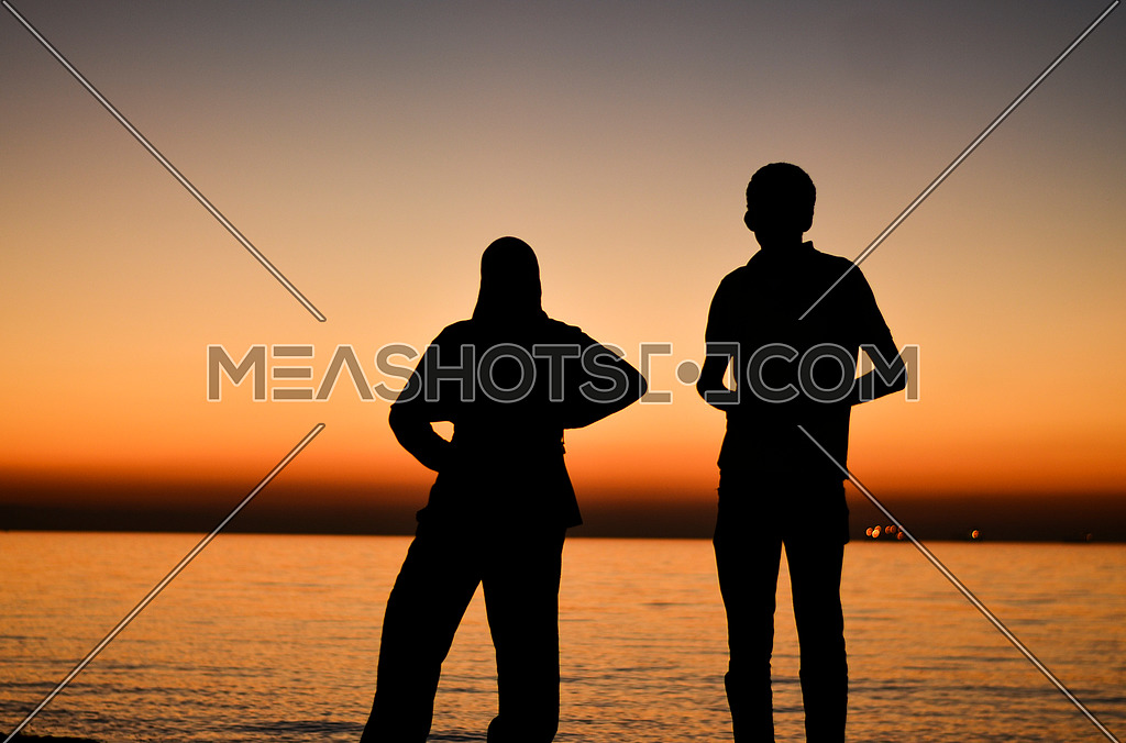 A Guy and a girl enjoying the scene of sunset at the beach