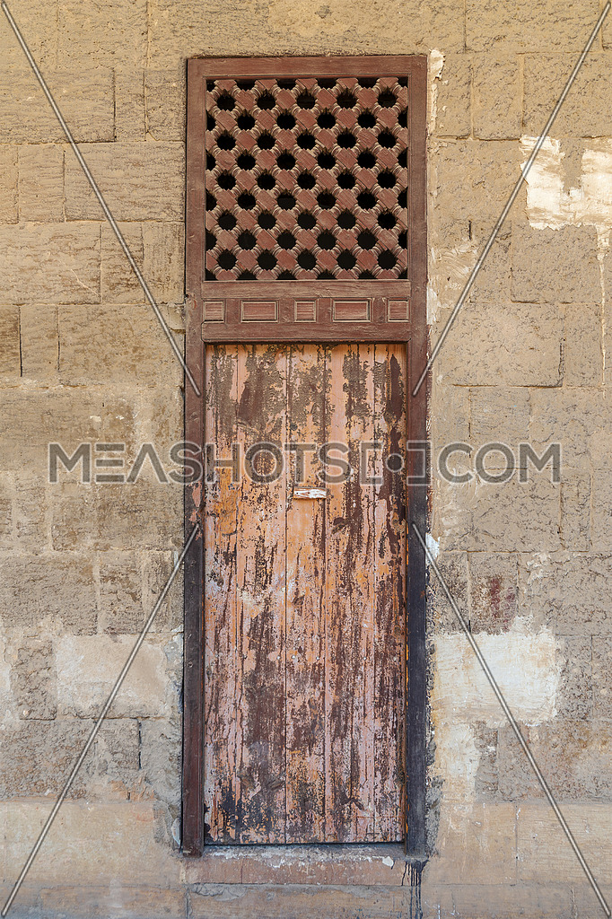 Facade of old abandoned stone bricks wall with weathered wooden door and windows covered with wooden grid, Old Cairo, Egypt