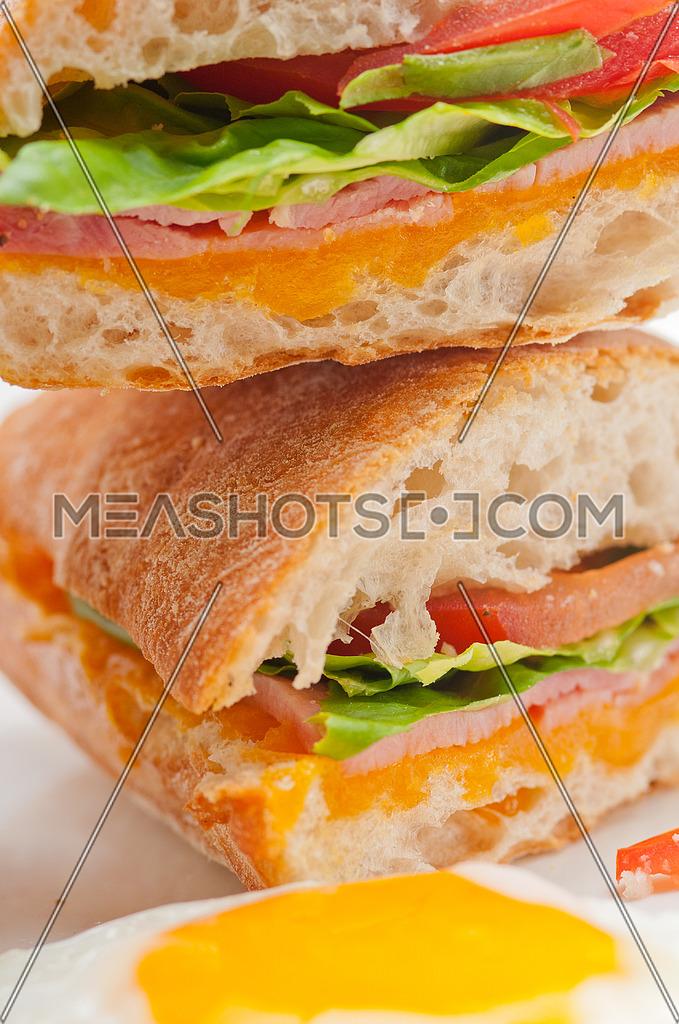 fresh ciabatta panini sandwich with eggs tomato lettuce