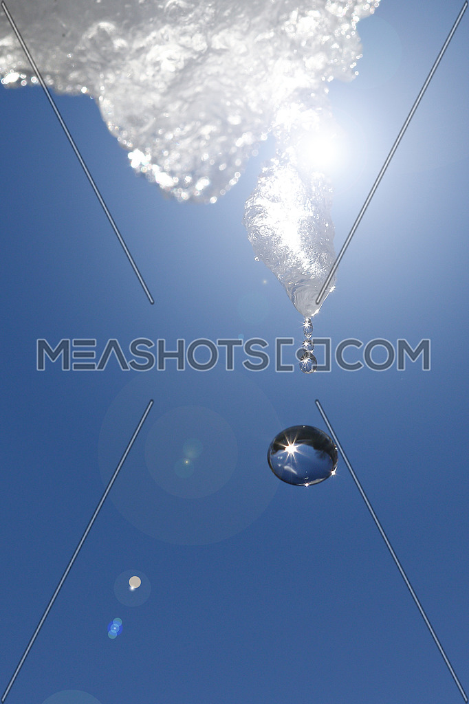 Icicle dripping against blue skies with reflections of the sun in water droplets