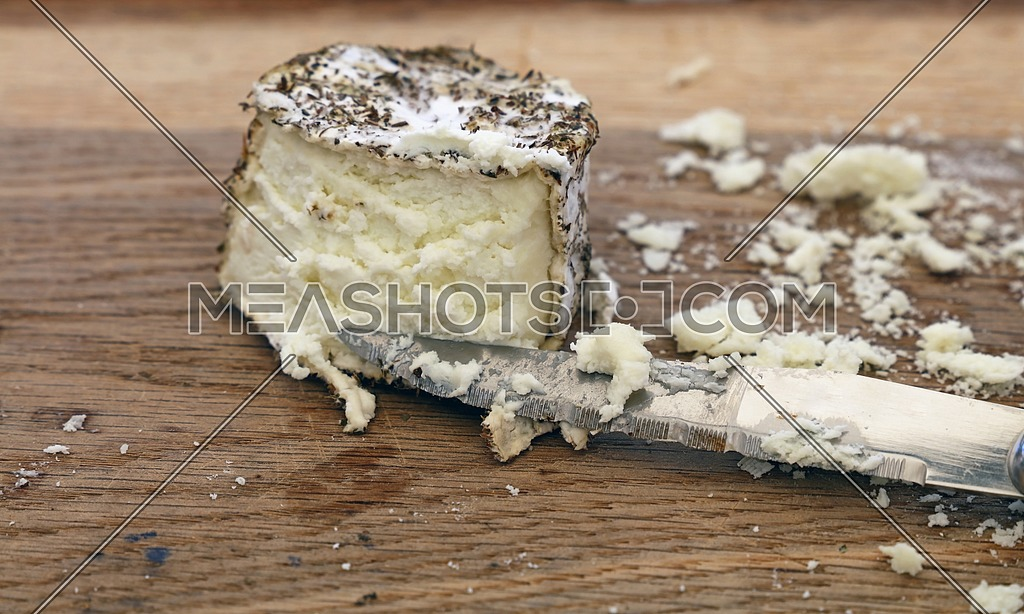 Close up one cut fresh French artisan gourmet goat cheese with herb spices and knife on wooden cutting board, high angle view