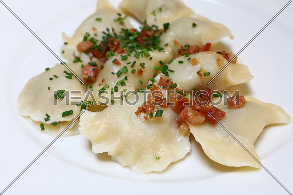 Plate of pierogi or varenyky stuffed filled dumplings with bacon and green chive onion, traditional East Europe cuisine meal popular in Poland, Ukraine, Slovakia, Russia, close up, high angle view