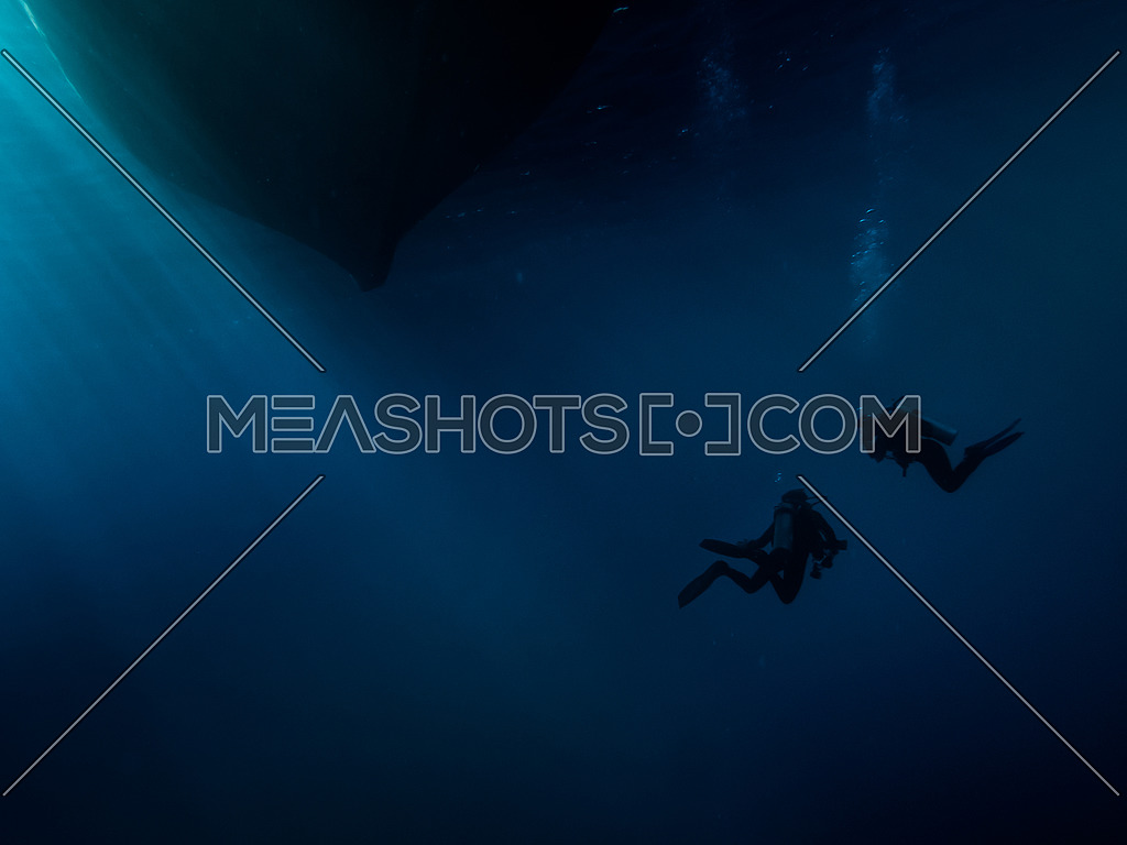 2 scuba divers below a boat bottom underwater