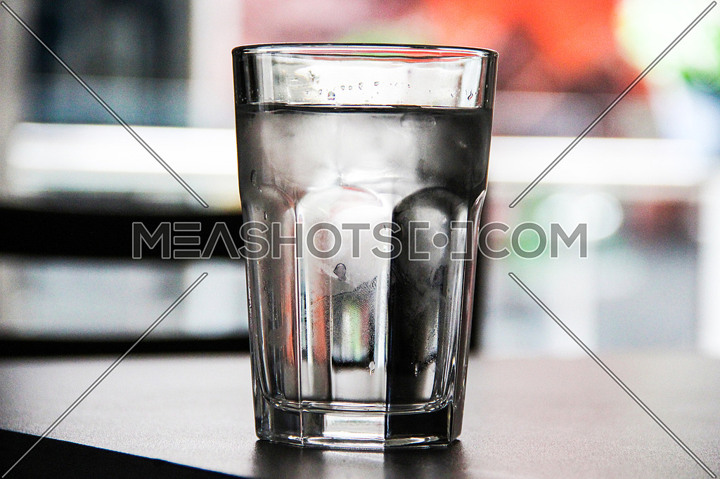 A cold glass of water in a dramatic lighting