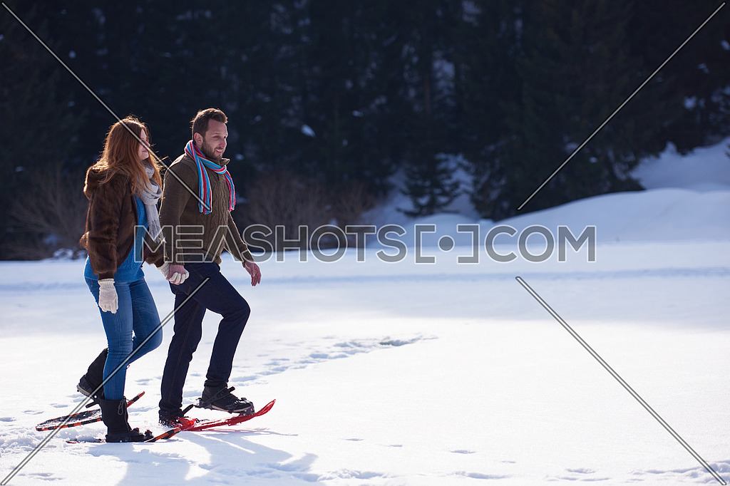 happy young couple having fun and walking in snow shoes. Romantic winter relaxation scene