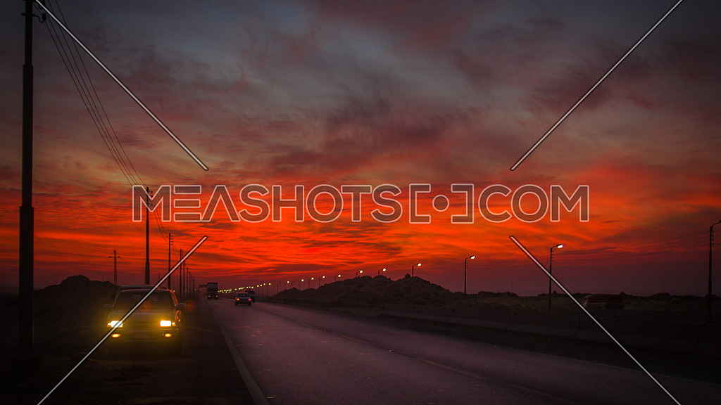 A car parked on the side of a Motorway at sunset
