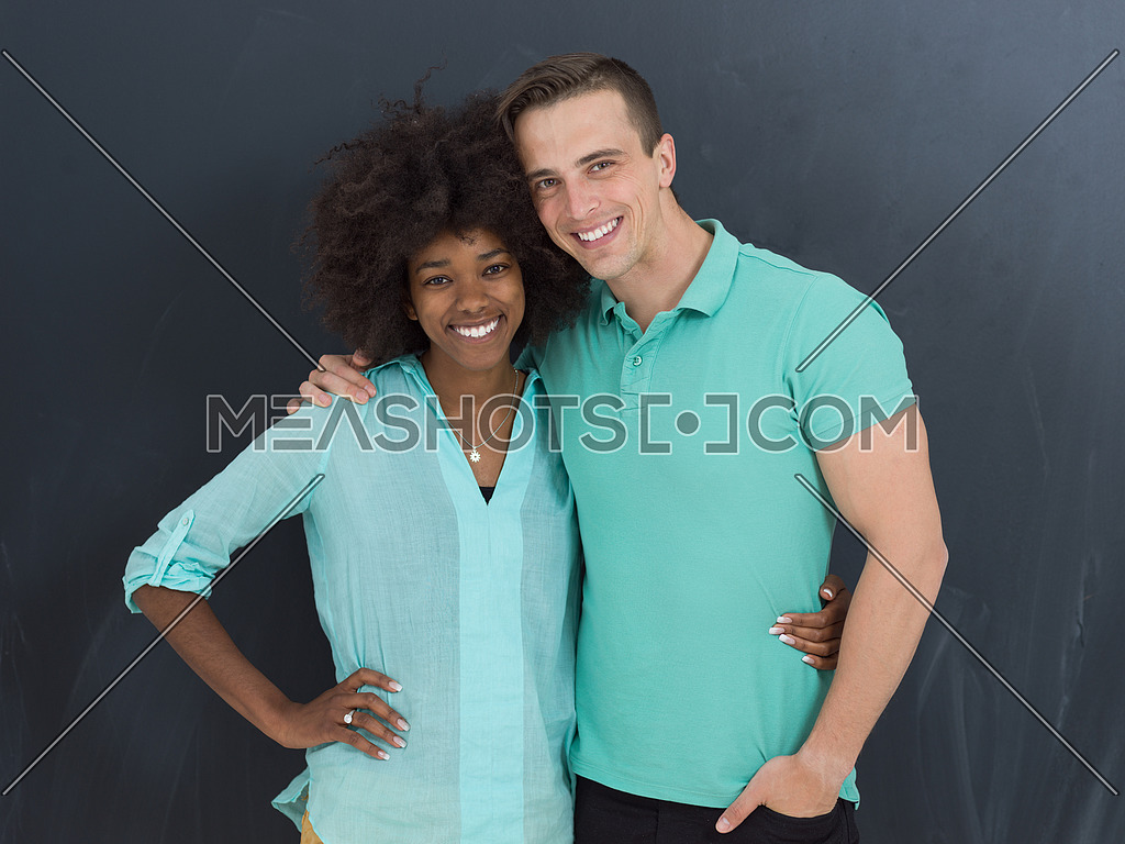 Young happy multiethnic couple laughing and hugging in front of gray chalkboard