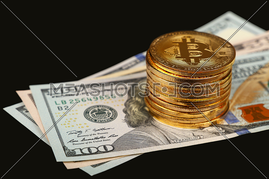 Close up stack of golden bitcoin physical coins on top of US dollar paper banknotes isolated on black background with copy space, high angle view, selective focus