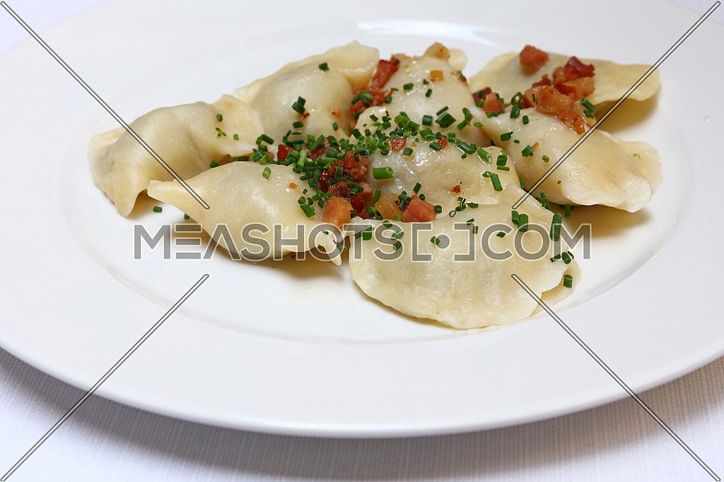 Plate of pierogi or varenyky stuffed filled dumplings with bacon crisps and green chive onion, traditional East Europe cuisine meal popular in Poland, Ukraine, Slovakia, Russia, close up, high angle view