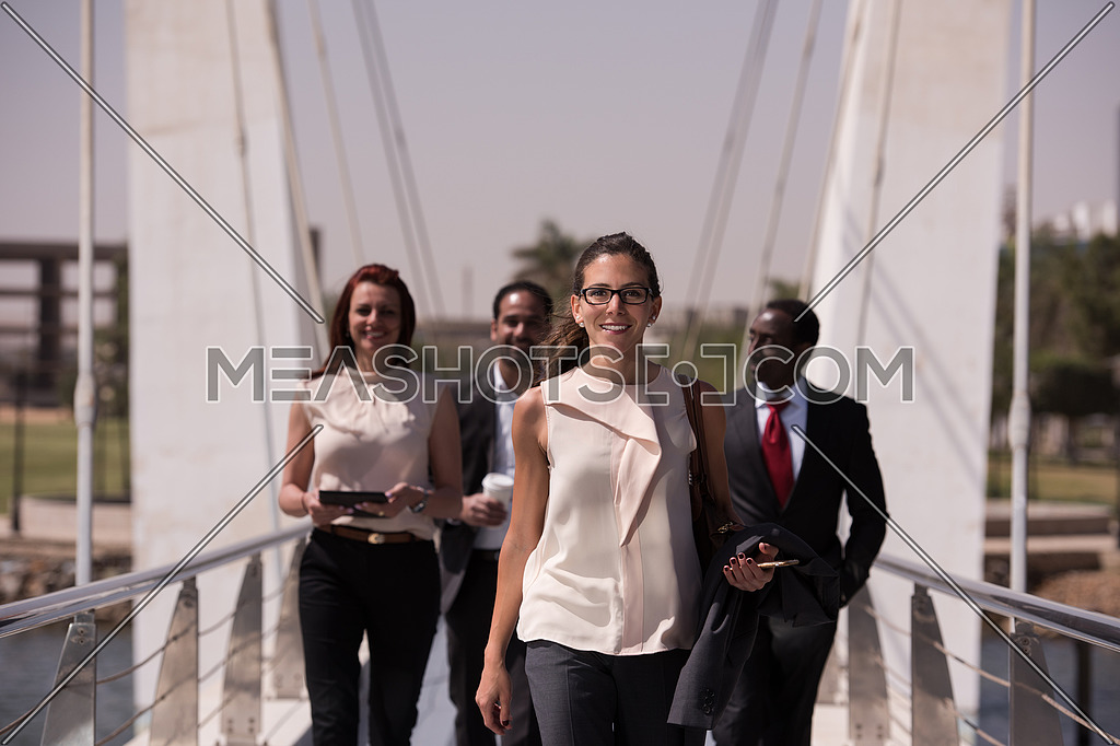 young multi ethnic business people group walking across modern bridge and drink first morning coffee