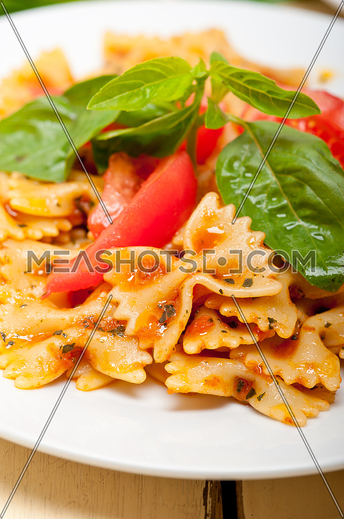 Italian pasta farfalle butterfly bow-tie with tomato basil sauce over white rustic wood table
