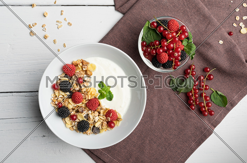 Healthy breakfast of two bowls, one with yogurt, muesli, raspberry and cherries, the other with mixed fruits on a background of violet tablecloth and white table