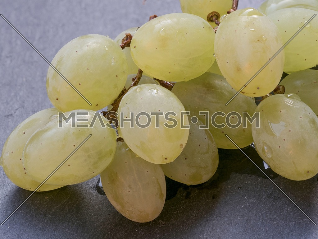 White grapes on dark surface. Food and healthy lifestyle concept. Fresh and delicious summer fruit composition. Macro shot