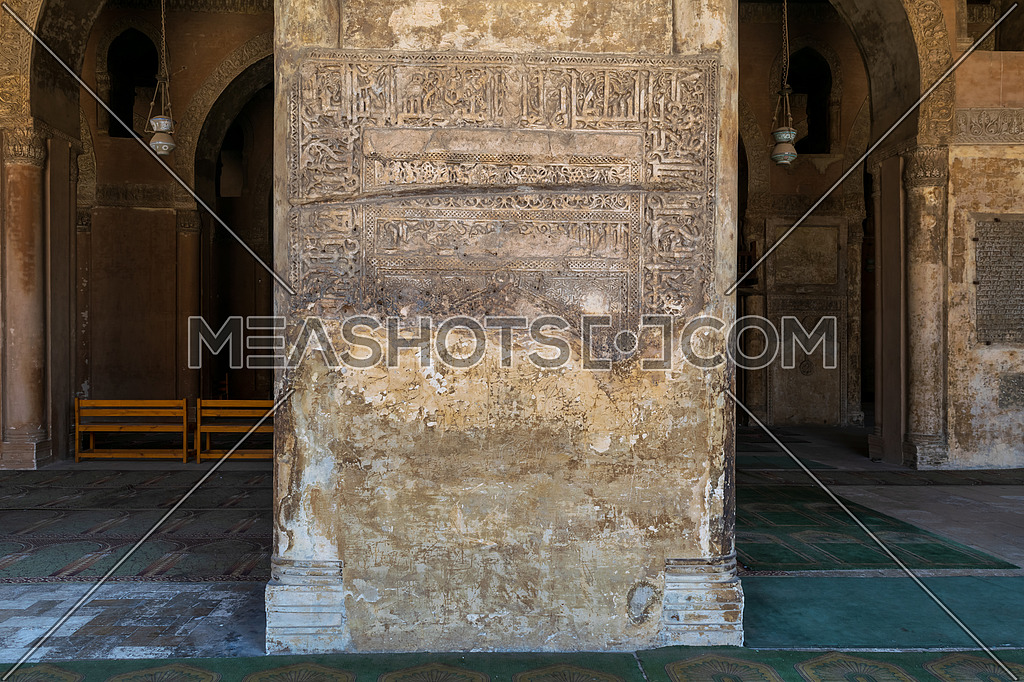 Ornate engraved stone wall with ruined floral patterns at Ahmed Ibn Tulun Mosque, Cairo, Egypt