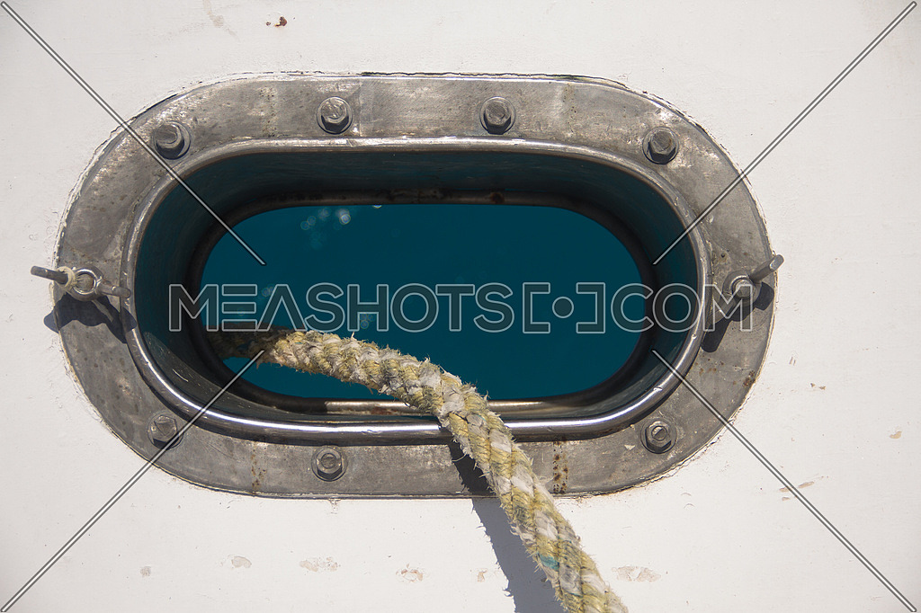 An opening in a ship shows the anchor rope