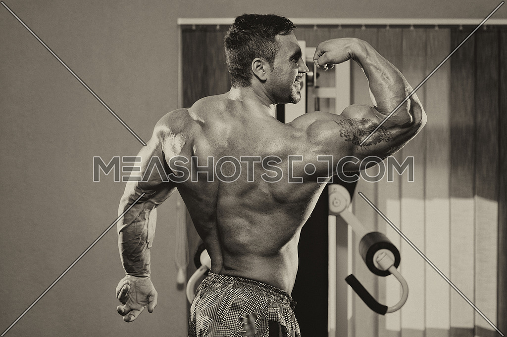 Bodybuilder Standing In The Gym And Flexing Muscles