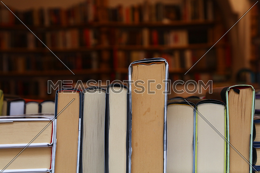 Close up hardcover books back edges on retail display of book store or shop