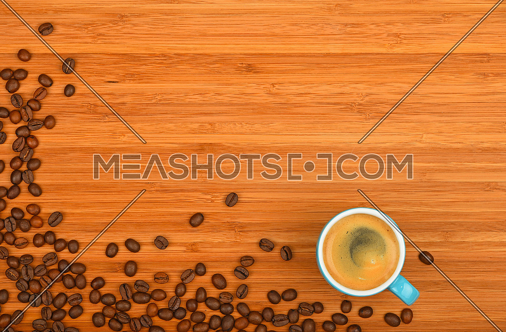 Blue coffee cup of espresso and roasted Arabica beans corner border shaped over wooden bamboo board background