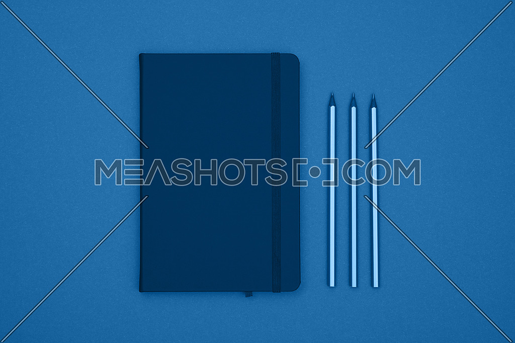 Close up one closed leather cover notebook and pencils over blue paper background, flat lay, directly above