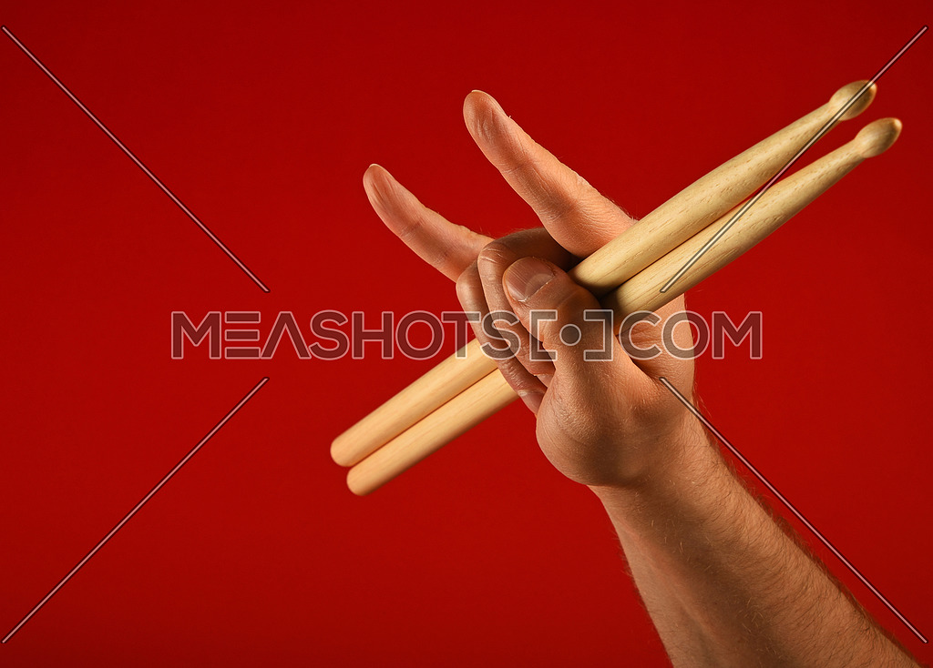 Man hand holding two drumsticks with devil horns rock metal gesture sign over red background