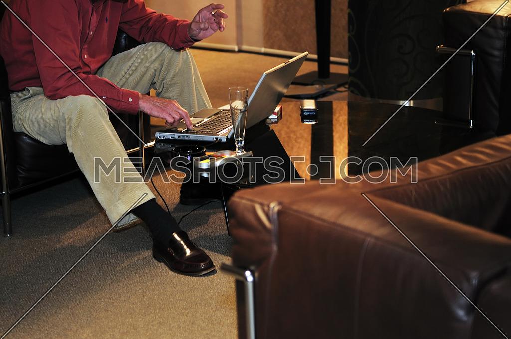 older senior businessman woking on laptop at hotel lobby