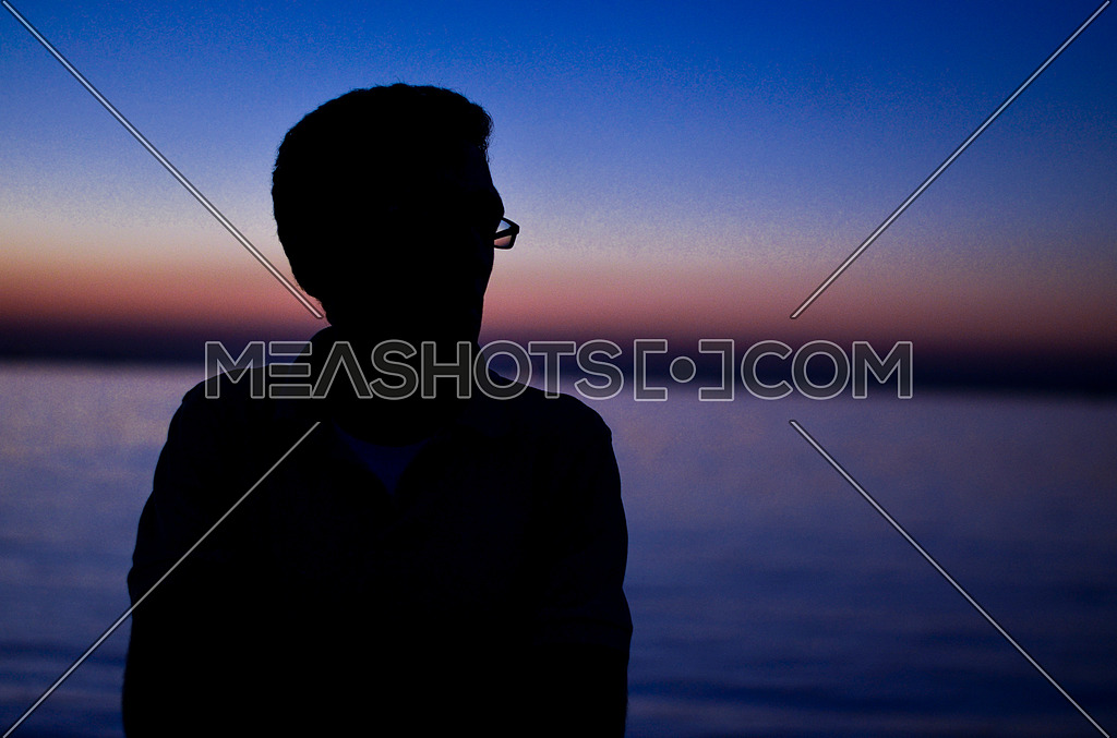 A guy standing at the beach enjoying his time and relaxing during sunrise time