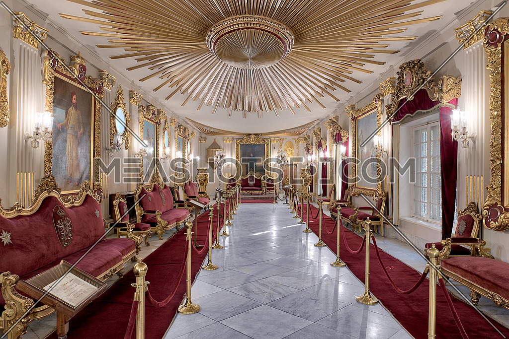 Throne Hall at Manial Palace of Prince Mohammed Ali Tewfik with ornate ceiling inspired by the old flag of the ottoman empire, gold plated armchairs, and red carpets, Cairo, Egypt