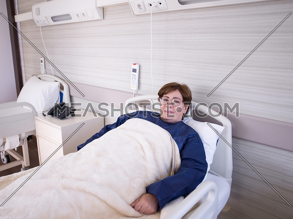 older woman as patient lies in hospital bed