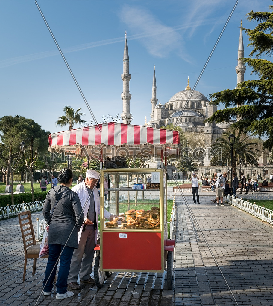 Tourist buying fast food meal from a traditional Turkish Simit