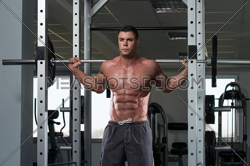 Young Man Performing Barbell Squats - One Of The Best Bodybuilding Exercise For Legs