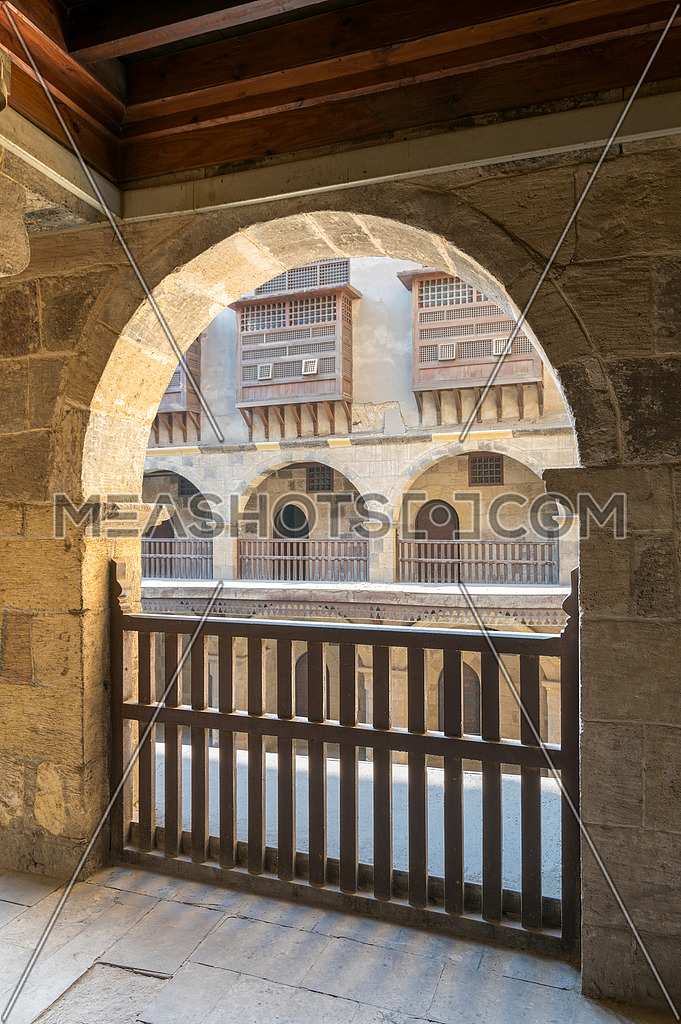 Arch with interleaved wooden balustrades at the arcade surrounding the courtyard of caravansary (Wikala) of Bazaraa, Medieval Cairo, Egypt