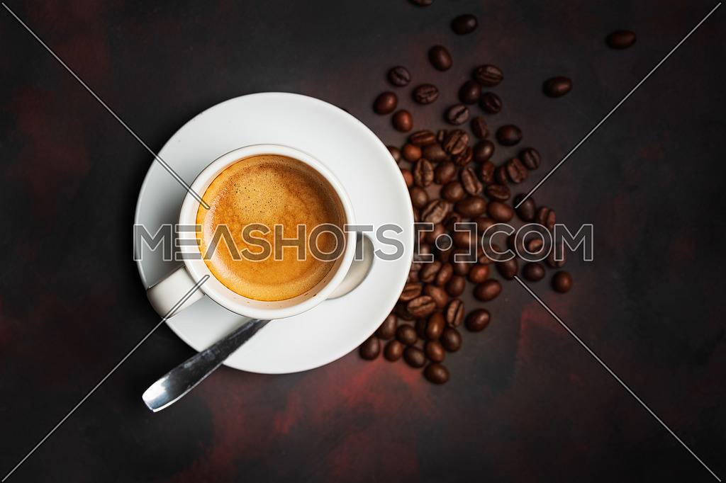 White cup of coffee and coffee bean on dark background. Copy space.view from above.