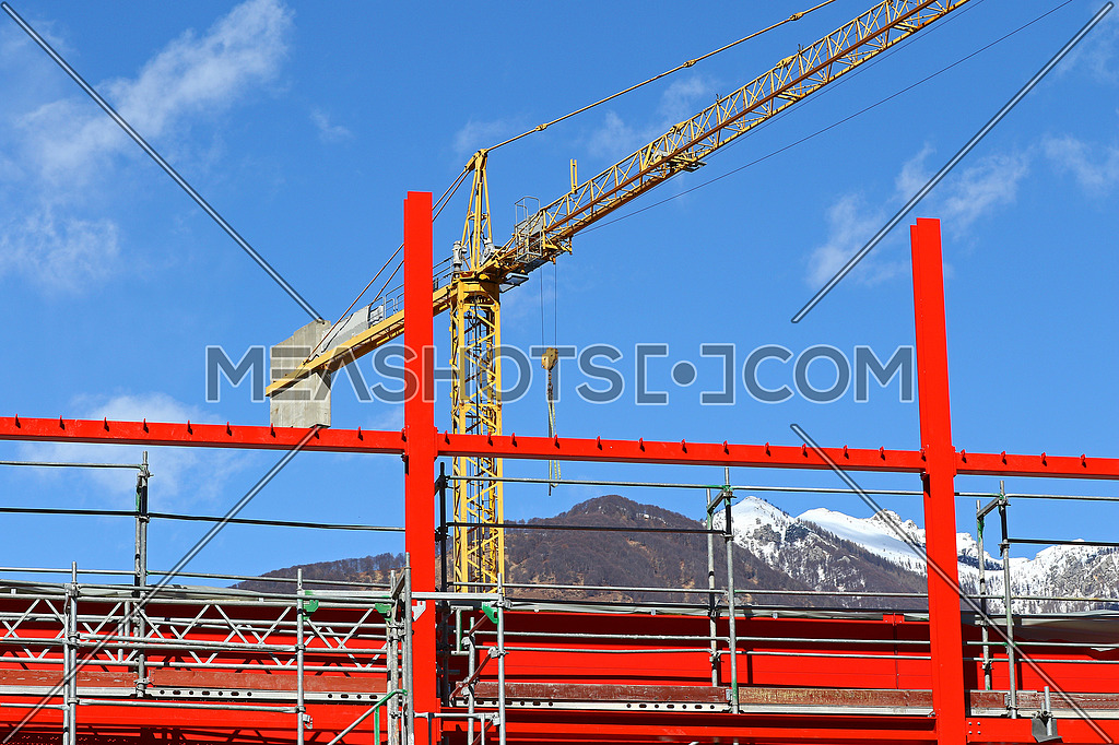 New steel beam construction being built with yellow crane against blue skies and white clouds