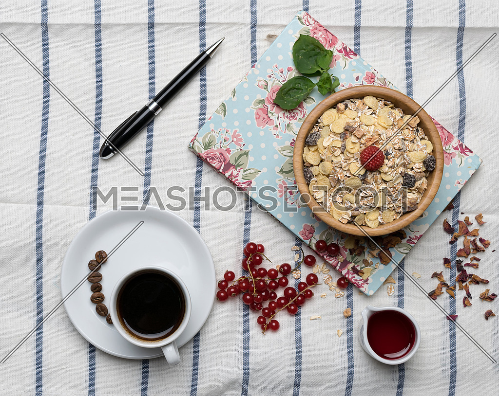 Healthy breakfast with muesli, raspberry, cherries and coffee on a background of white table cloth, block note, and black pen