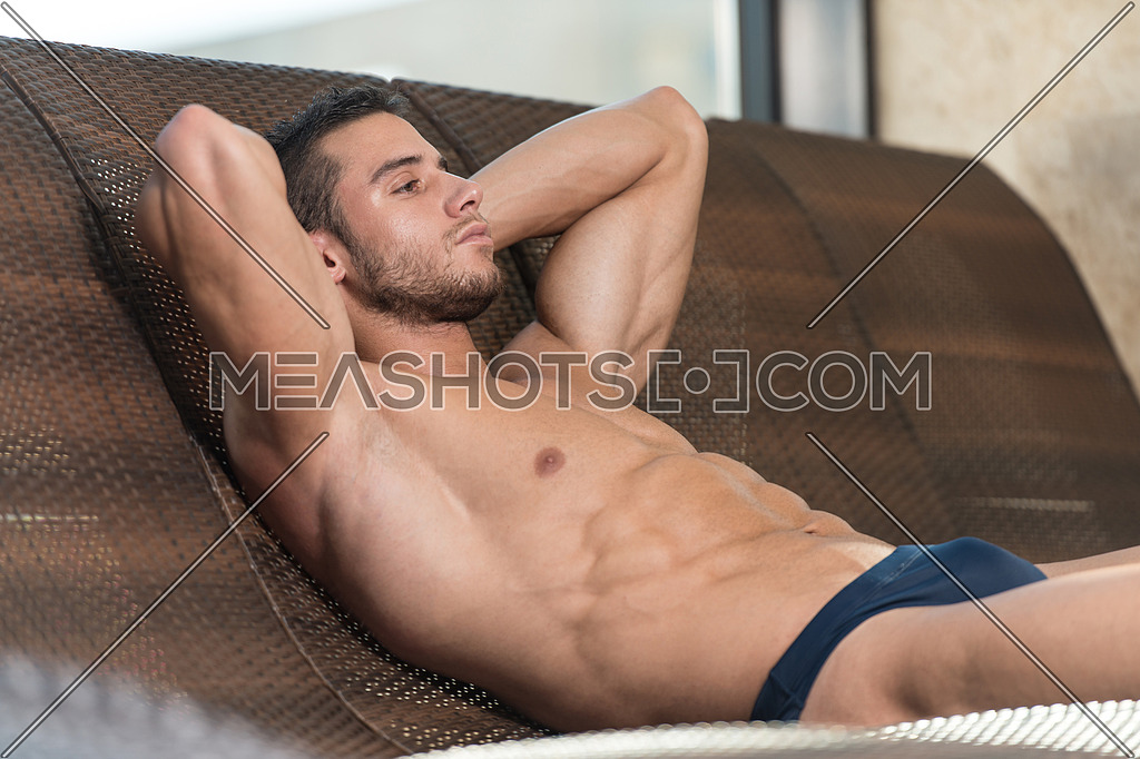 Young Man Resting On Sun Loungers By Swimming Pool And Flexing Muscles