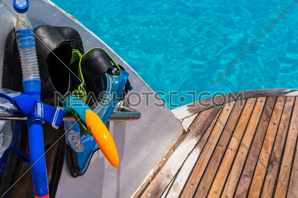 In the pictured boat with curved wooden deck wet,on the left fins,mask,scuba rubber for snorkeling and in the background ocean blue / turquoise.