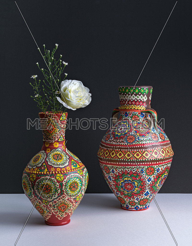 Still life composition of two colorful pottery vases, white flower, and small flowers on background of white table and dark wall